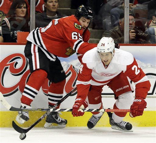 Detroit Red Wings' Damien Brunner (24) controls the puck against Chicago Blackhawks' Andrew Shaw (65) during the second period of Game 2 of the NHL hockey Stanley Cup playoffs Western Conference semifinals in Chicago, Saturday, May 18, 2013