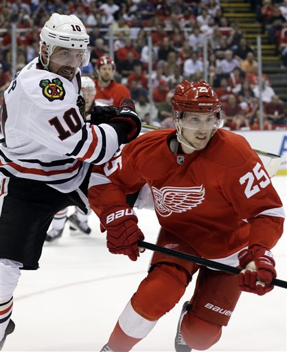 Chicago Blackhawks center Patrick Sharp (10) and Detroit Red Wings center Cory Emmerton (25) battle for the puck during the first period of an NHL hockey Stanley Cup playoffs Western Conference semifinal game in Detroit, Monday, May 20, 2013
