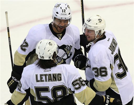 Pittsburgh Penguins' Jarome Iginla (12) celebrates a third period goal with teammates Kris Letang (58) and Jussi Jokinen (36) during NHL hockey playoff game action against the Ottawa Senators in Ottawa, Ontario, Wednesday, May 22, 2013