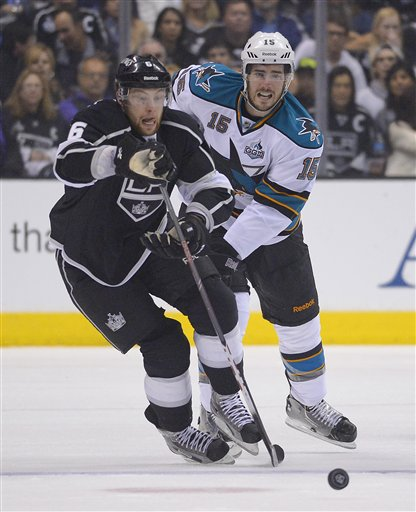 Los Angeles Kings defenseman Jake Muzzin (6) and San Jose Sharks center James Sheppard (15) race after the puck in the first period during Game 5 of the Western Conference semifinals in the NHL hockey Stanley Cup playoffs, Thursday, May 23, 2013, in Los Angeles