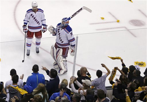 As Boston Bruins fans celebrate, New York Rangers goalie Henrik Lundqvist (30) and center Derick Brassard skate downice after losing 2-1 to the Bruins, eliminating the Rangers from the NHL playoffs in Game 5 of the Eastern Conference semifinals in the NHL hockey Stanley Cup playoffs in Boston, Saturday, May 25, 2013