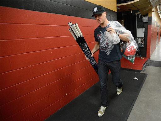 Ottawa Senators' Marc Methot carries hockey sticks during a locker room clean out day in Ottawa on Monday, May 27, 2013
