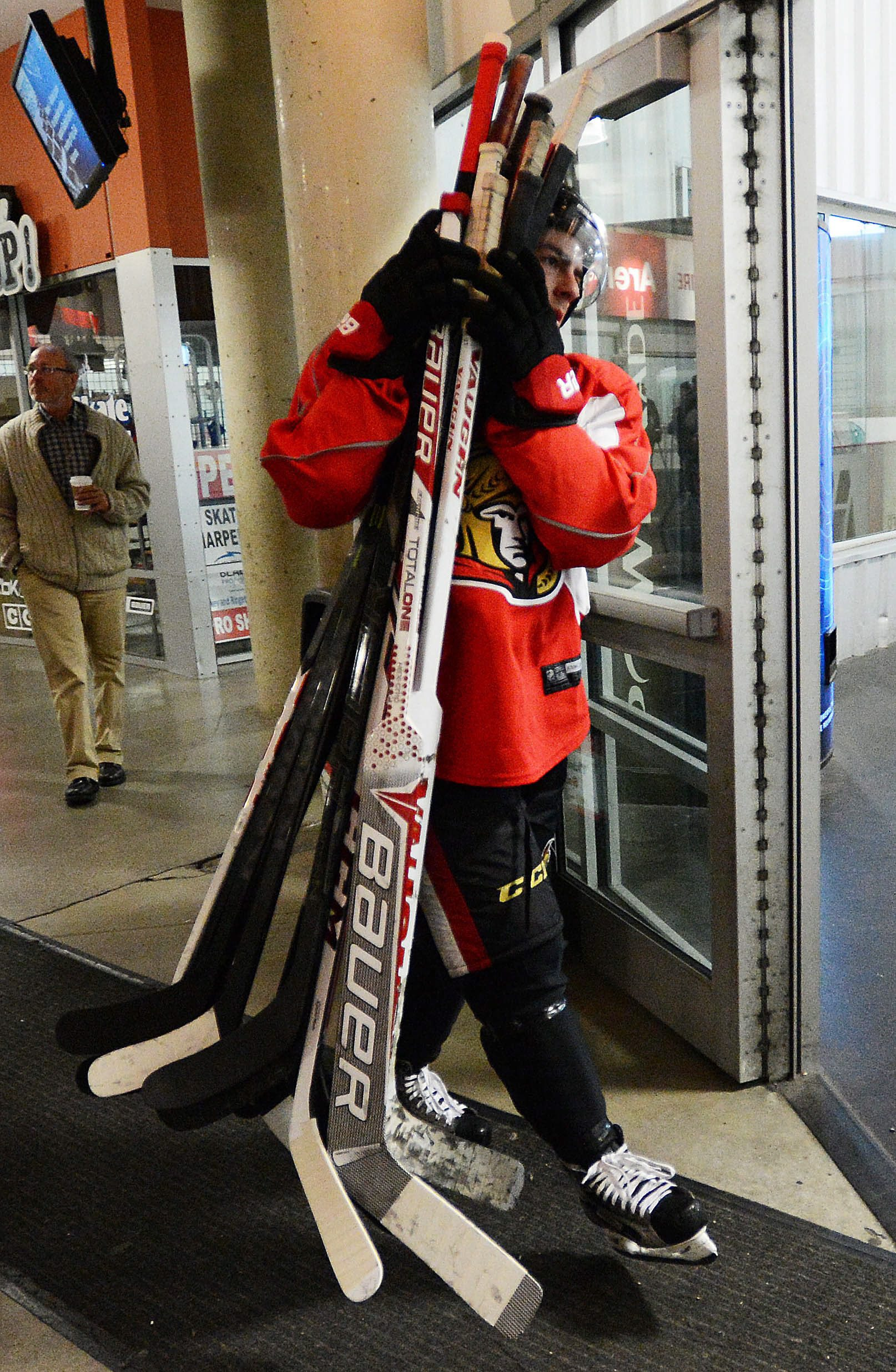 Ottawa Senators' Jean-Gabriel Pageau carries his teammates sticks as they change ice surfaces during the team's NHL hockey training camp in Ottawa,  on Thursday, Sept. 12, 2013