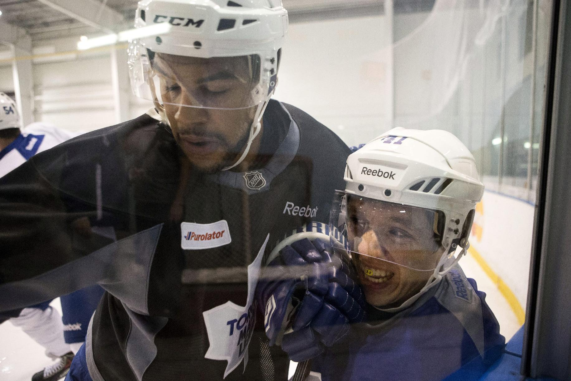Toronto Maple Leafs' Nikolai Kulemin, left, battles along the boards with Mark Fraser during a scrimmage at NHL hockey training camp in Toronto on Friday, Sept. 13, 2013