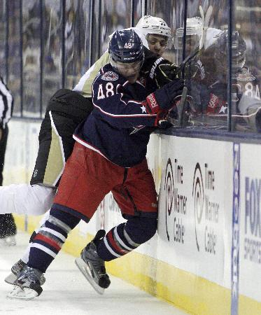 Blue Jackets' Cody Goloubef, front, checks Pittsburgh Penguins' Evgeni Malkin, of Russia, during the first period of an NHL preseason hockey game, Sunday, Sept. 15, 2013, in Columbus, Ohio