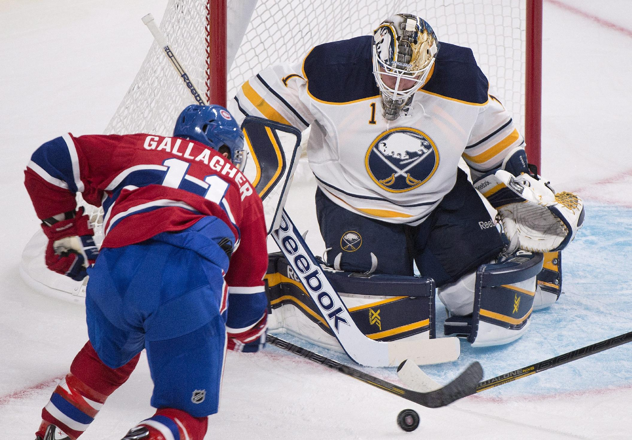 Buffalo Sabres' goaltender Jhonas Enroth, right, makes a save against Montreal Canadiens' Brendan Gallagher during the first period of an NHL pre-season hockey game, Sunday, Sept. 15, 2013 in Montreal
