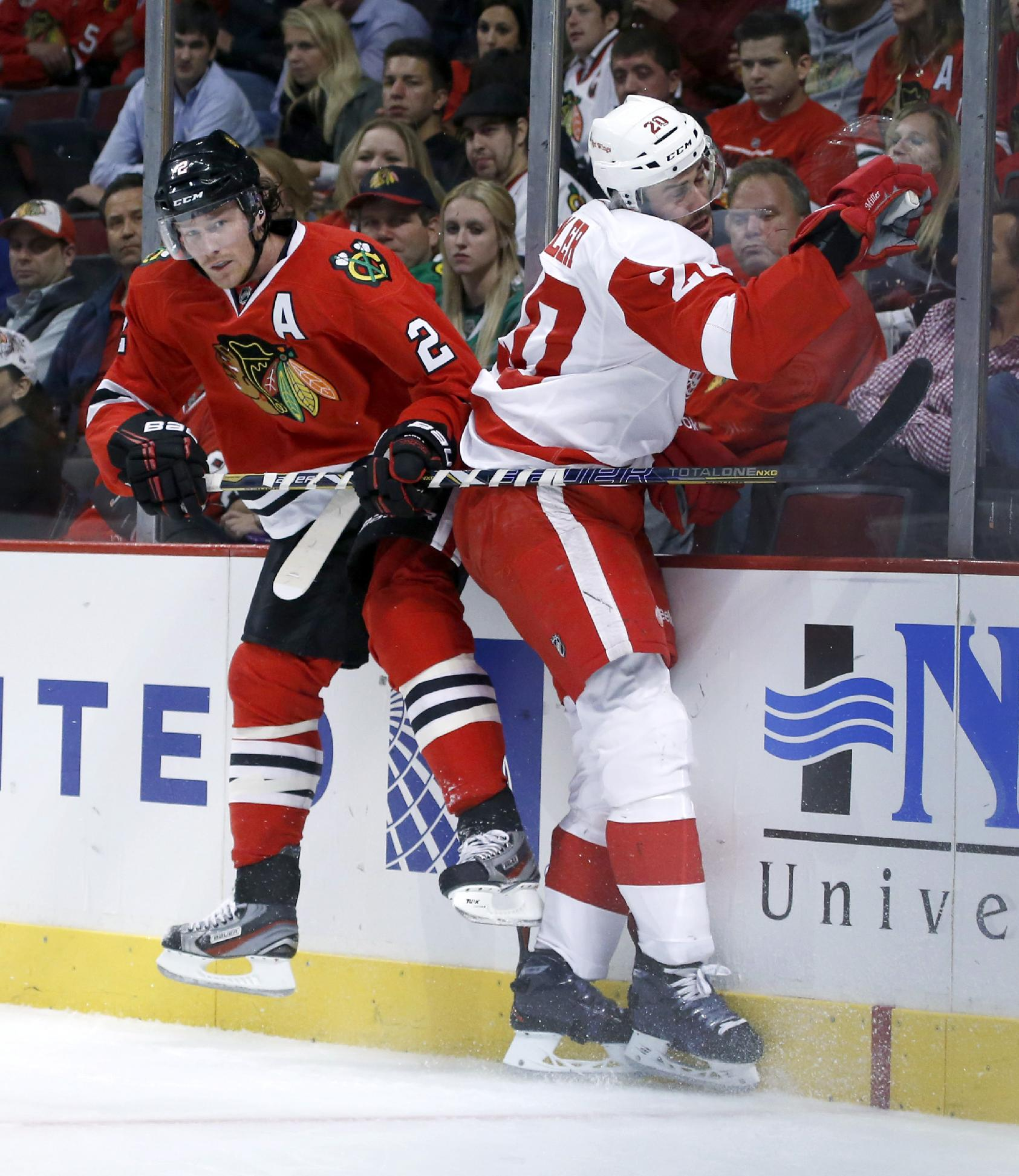 Chicago Blackhawks defenseman Duncan Keith, left, checks Detroit Red Wings left wing Drew Miller into the boards during the first period of an NHL preseason hockey game Tuesday, Sept. 17, 2013, in Chicago
