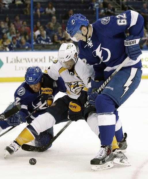 Tampa Bay Lightning defenseman Andrej Sustr (62) and left wing Ryan Malone (12) team up to take down Nashville Predators center Matt Cullen (7) during the first period of an NHL preseason hockey game, Thursday, Sept. 19, 2013, in Tampa, Fla
