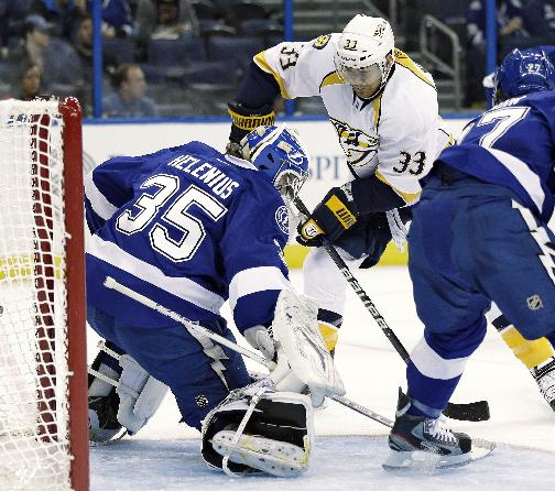 Tampa Bay Lightning goalie Riku Helenius (35), of Finland, makes a save on a shot by Nashville Predators center Colin Wilson (33) during the first period of an NHL preseason hockey game, Thursday, Sept. 19, 2013, in Tampa, Fla. Tampa Bay's Jonathan Drouin defends