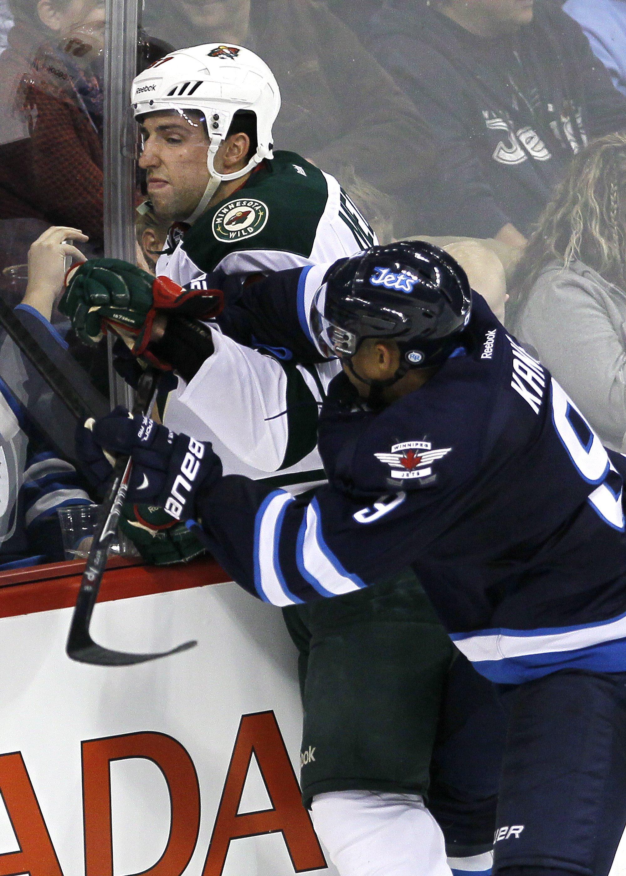 Winnipeg Jets' Evander Kane (9) takes out Minnesota Wild's Kyle Medvec (67) during third-period preseason NHL hockey game action in Winnipeg, Manitoba, Thursday, Sept. 19, 2013