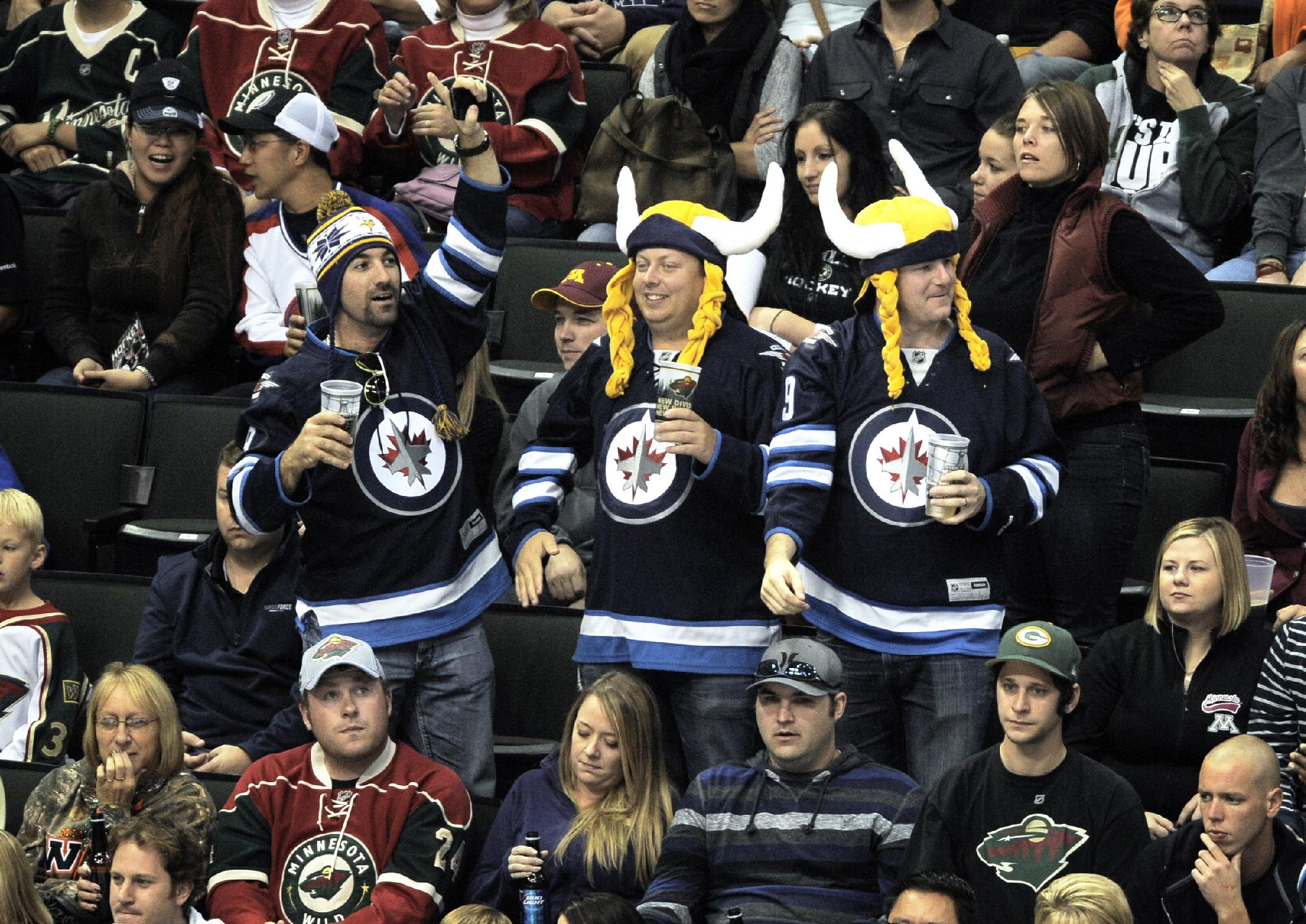 Winnipeg Jets fans wearing Minnesota Vikings headgear celebrate a goal by Jet's Jerome Samson in the second period of an NHL hockey game against the Minnesota Wild, Saturday, Sept. 21, 2013, in St. Paul, Minn. Minnesota won 4-3 in a shootout. The Minnesota Vikings are to play the Cleveland Browns on Sunday at Mall of America field in Minneapolis