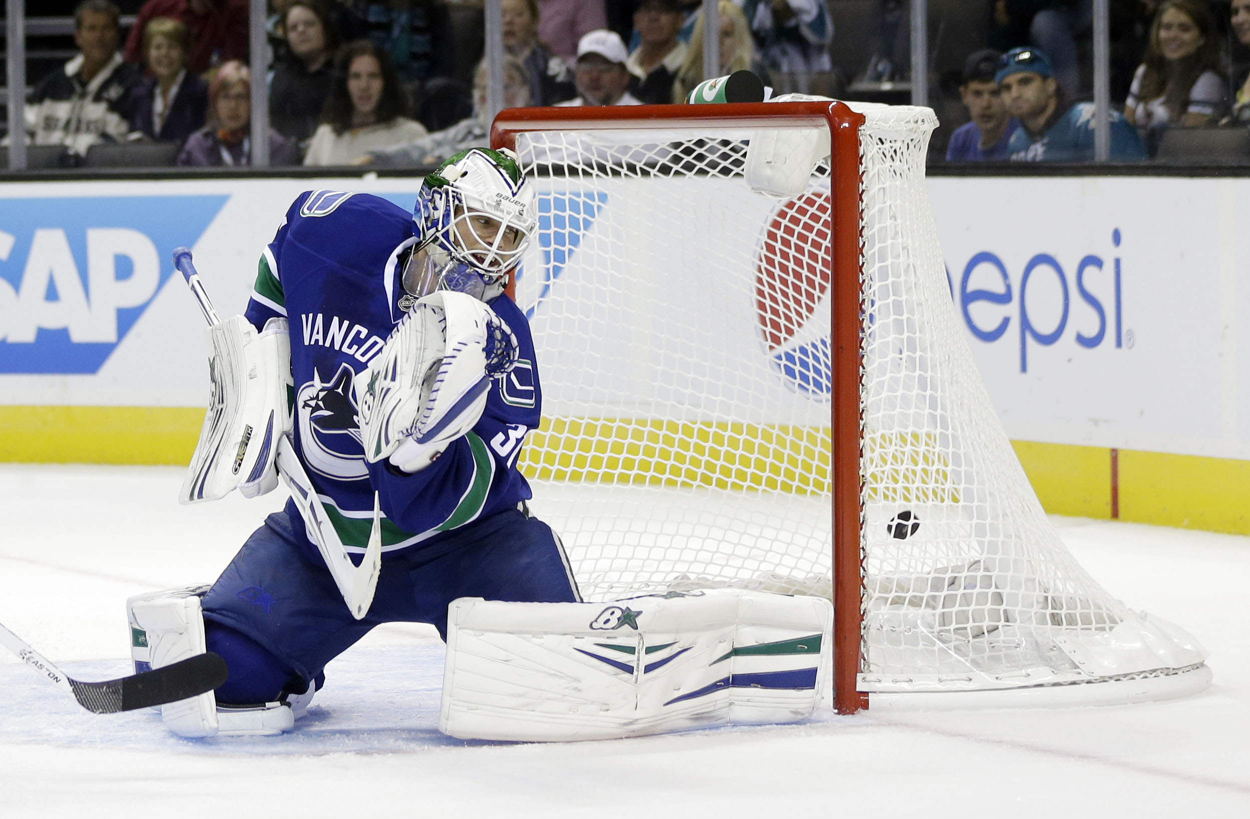 Vancouver Canucks goalie Eddie Lack is beaten for a goal on a shot from San Jose Sharks defenseman Dan Boyle during the first period of a preseason NHL hockey game on Tuesday, Sept. 24, 2013, in San Jose, Calif