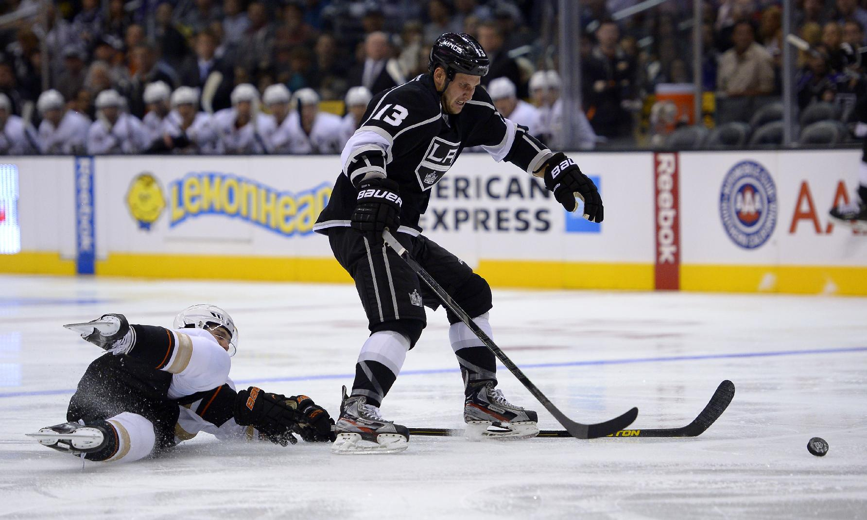 Los Angeles Kings left wing Kyle Clifford, right, takes the puck as Anaheim Ducks defenseman Ben Lovejoy reaches in during the second period of their NHL preseason hockey game, Tuesday, Sept. 24, 2013, in Los Angeles