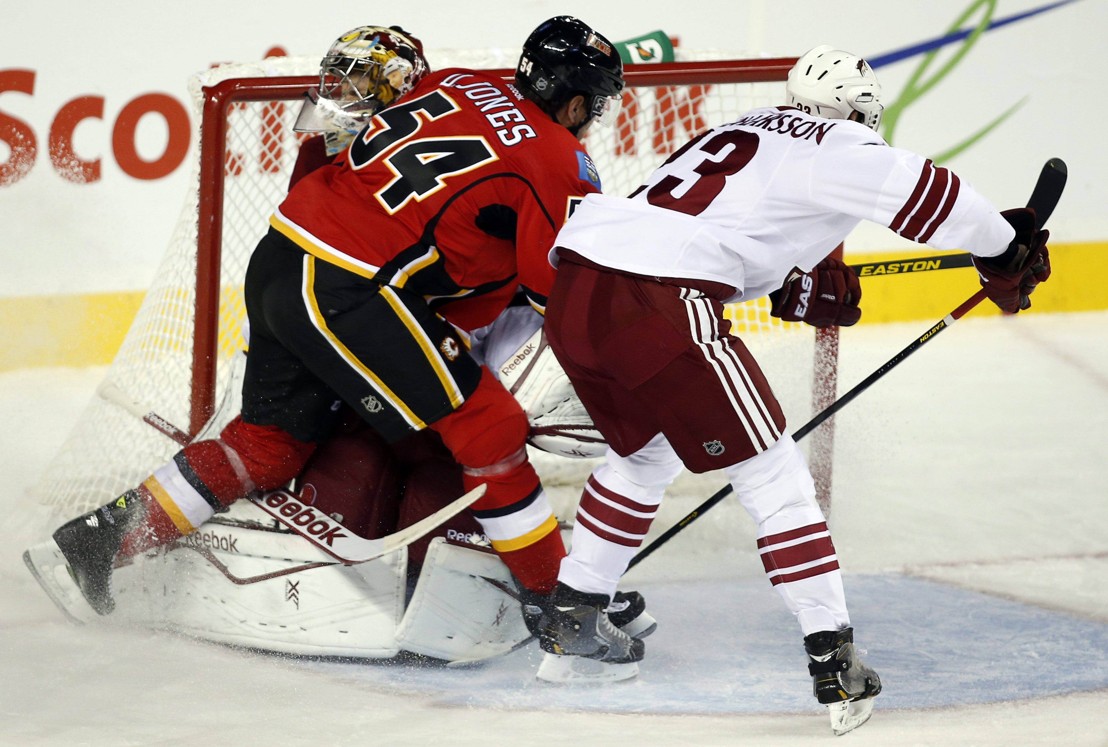 Phoenix Coyotes goalie Mike Smith, left, is slammed into the net by Calgary Flames' David Jones (54) as Coyotes' Oliver Ekman-Larsson, from Sweden, looks on during second-period NHL preseason hockey game action in Calgary, Alberta, Wednesday, Sept. 25, 2013