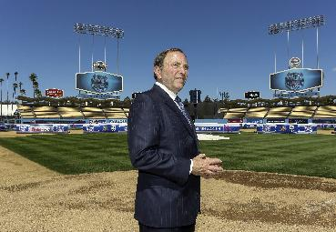 NHL Commissioner Gary Bettman walks to home plate at Dodger Stadium, after a news conference Thursday, Sept. 26, 2013, in Los Angeles. Bettman announced an outdoor hockey game between the Los Angeles Kings and the Anaheim Ducks. The game will be played on a temporary rink at the baseball field on Jan. 25, 2014