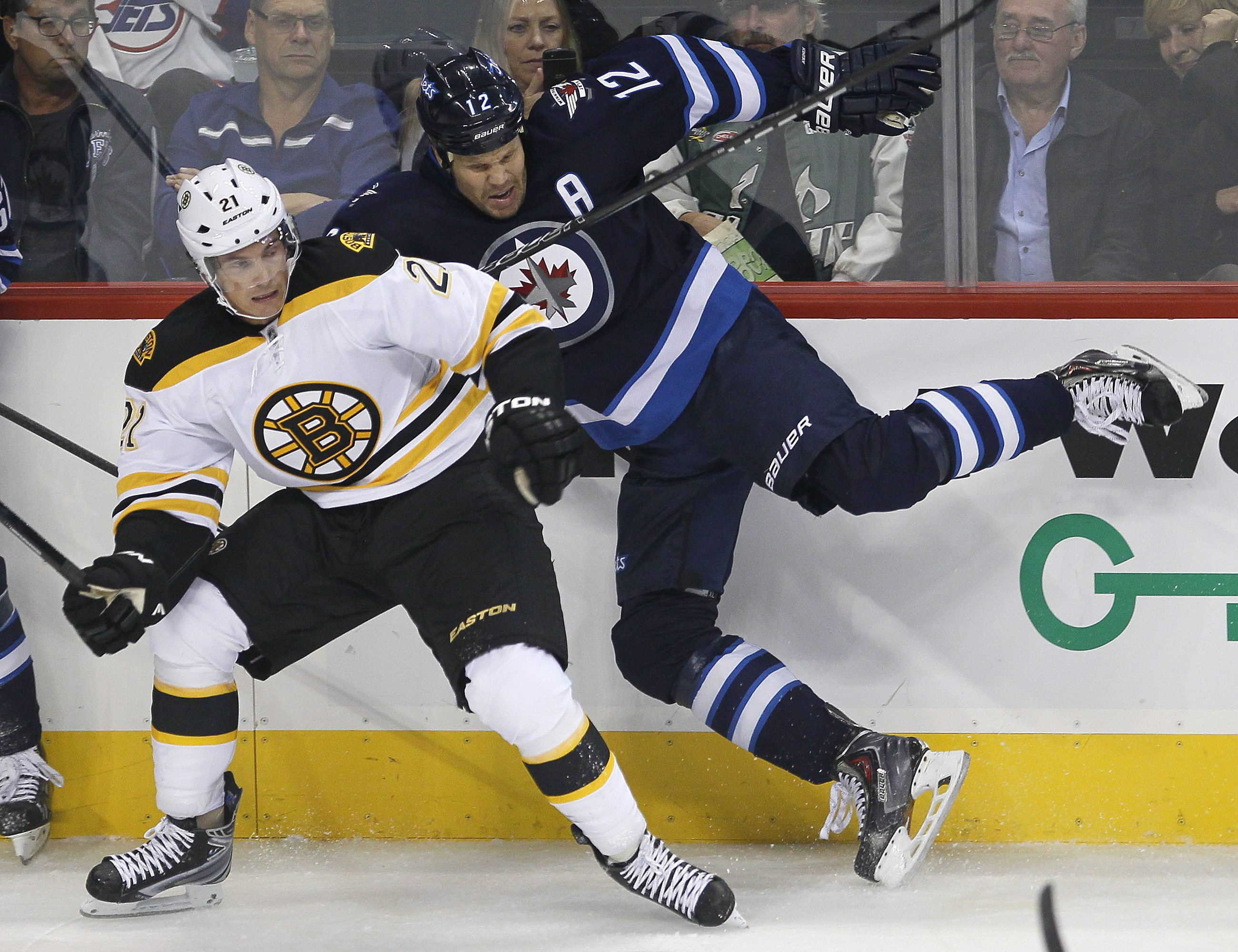 Boston Bruins' Loui Eriksson, left, takes out Winnipeg Jets' Olli Jokinen during the first period of a preseason NHL hockey game Thursday, Sept. 26, 2013, in Winnipeg, Manitoba
