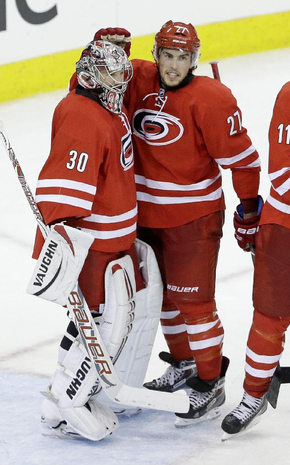 Carolina Hurricanes goalie Cam Ward (30) is congratulated by Justin Faulk (27) following the Hurricanes 1-0 win over the Buffalo Sabres in an NHL preseason hockey game on Friday, Sept. 27, 2013, in Raleigh, N.C