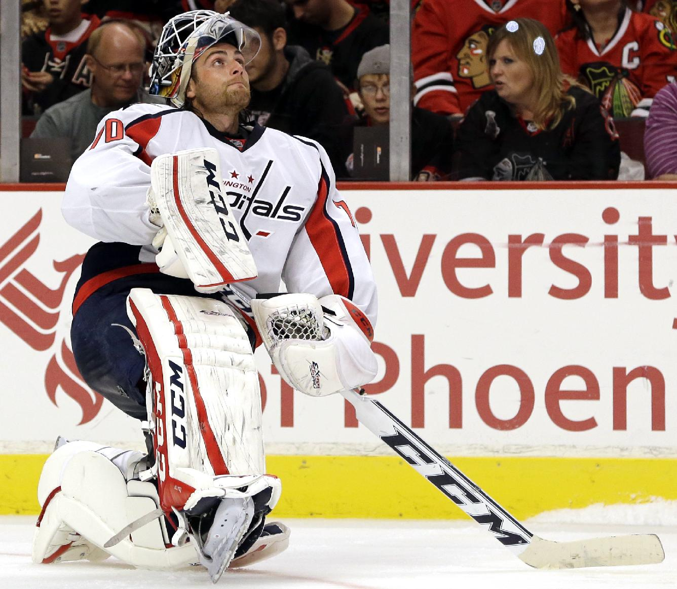 Washington Capitals goalie Braden Holtby stretches as he looks up the score board during the second period of an NHL preseason hockey game against the Chicago Blackhawks  in Chicago, Saturday, Sept. 28, 2013