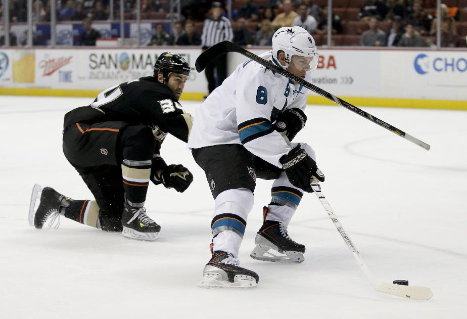 San Jose Sharks center Joe Pavelski, right, prepares to score with the stick of Anaheim Ducks left wing Daniel Winnik on his shoulder during the first period of an NHL hockey preseason game in Anaheim, Calif., Saturday, Sept. 28, 2013