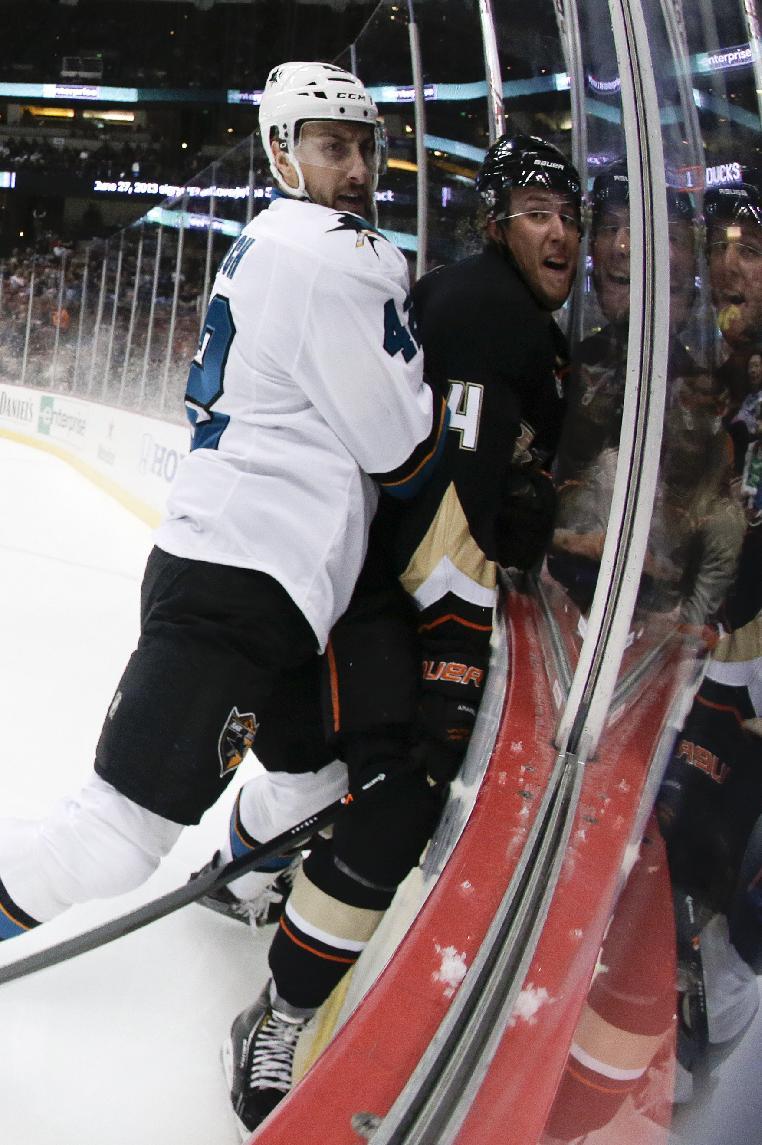 San Jose Sharks defenseman Matt Pelech, left, checks Anaheim Ducks defenseman Cam Fowler into the glass during the second period of an NHL hockey preseason game in Anaheim, Calif., Saturday, Sept. 28, 2013