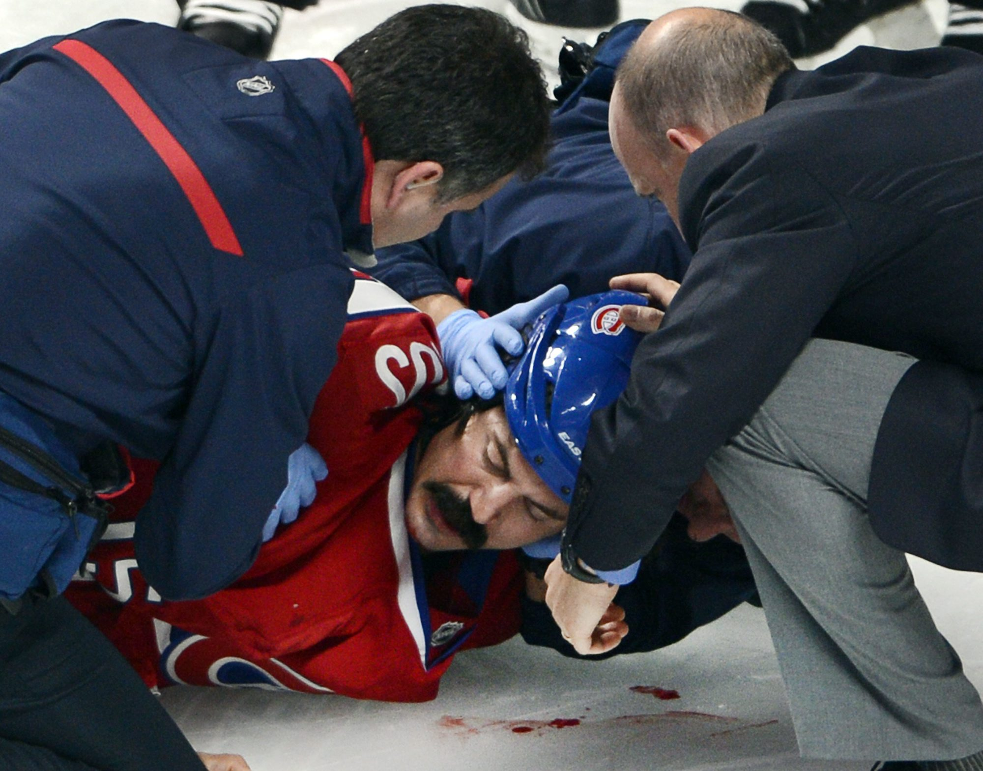 In this Oct. 1, 2013 photo, Montreal Canadiens winger George Parros (15) is treated by medical staff after he hit his head on the ice during a fight with Toronto Maple Leafs right wing Colton Orr during third period NHL action in Montreal. Parros sustained a concussion
