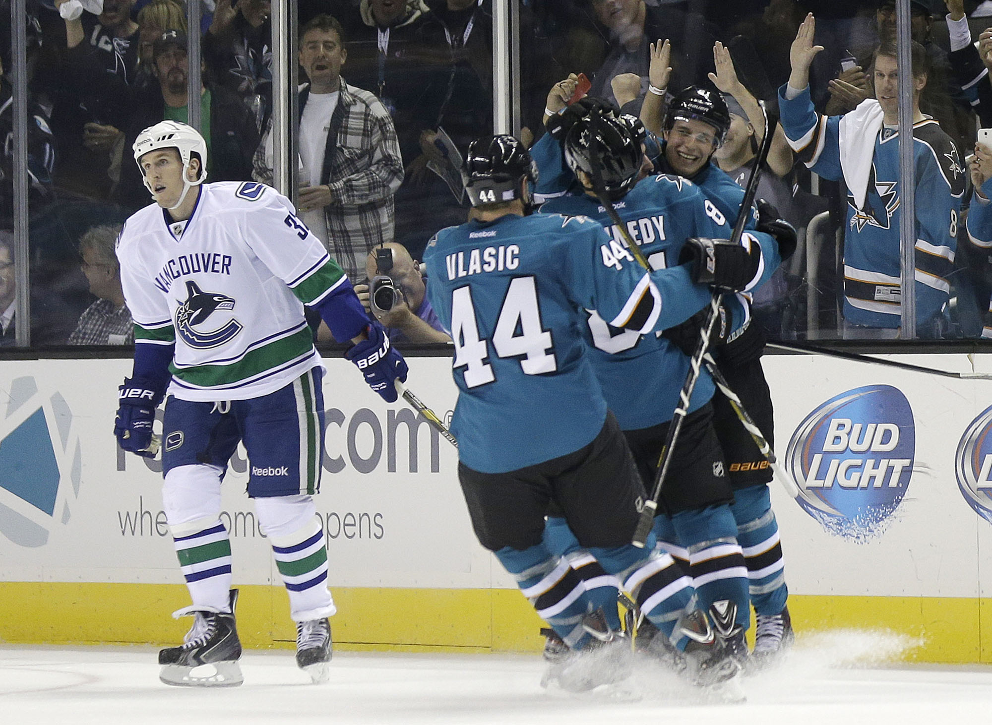 San Jose Sharks' Justin Braun, right, is hugged by teammates Tyler Kennedy and Marc-Edouard Vlasic (44) after scoring against the Vancouver Canucks during the second period of an NHL hockey game on Thursday, Oct. 3, 2013, in San Jose, Calif. Canucks' Dale Weise is at left