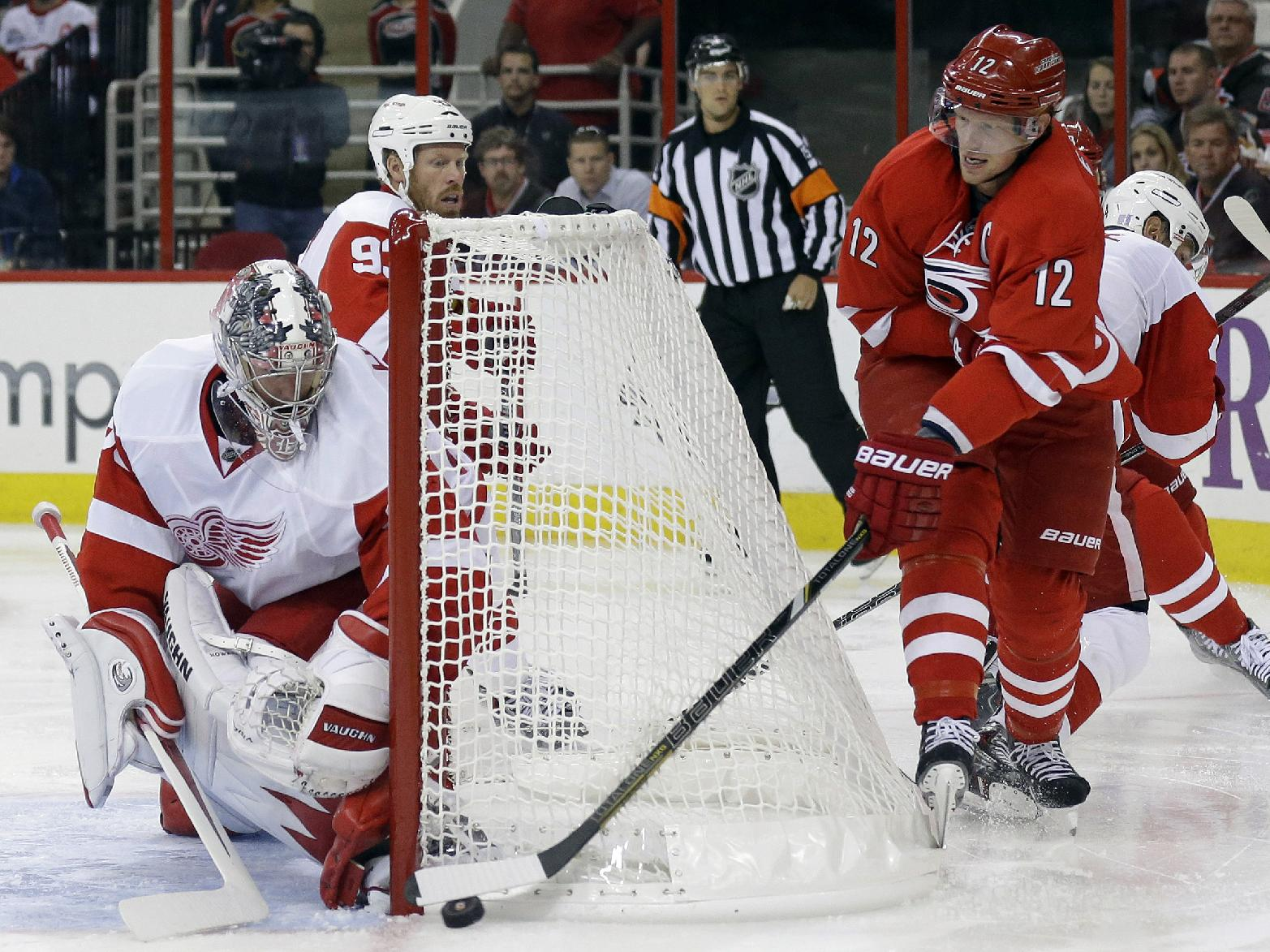 Detroit Red Wings goalie Jimmy Howard, left, defends the goal against Carolina Hurricanes' Eric Staal (12) during the second period of an NHL hockey game in Raleigh, N.C., Friday, Oct. 4, 2013