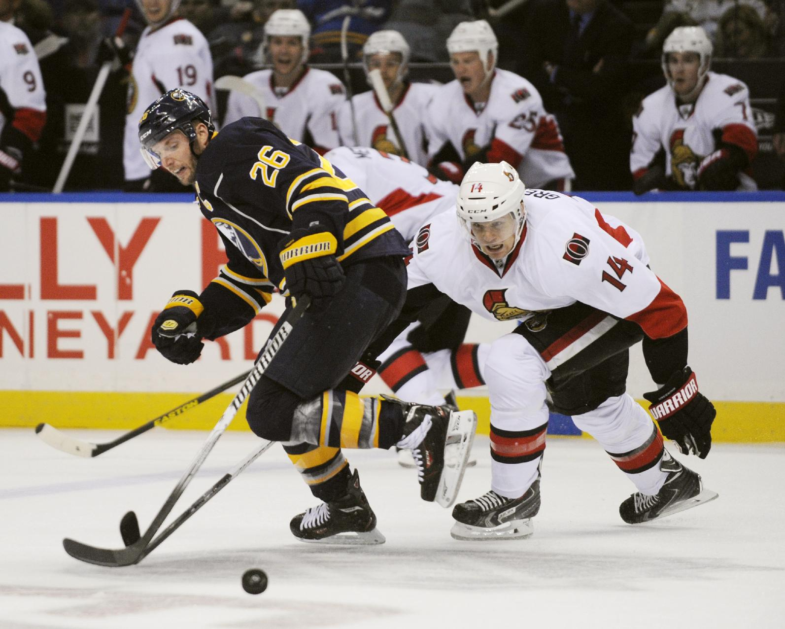 Buffalo Sabres'  Thomas Vanek (26), of Austria, gets stripped of the puck by Ottawa Senators' Colin Greening (14) during the second period of a NHL hockey game in Buffalo, N.Y., Friday, Oct. 4, 2013