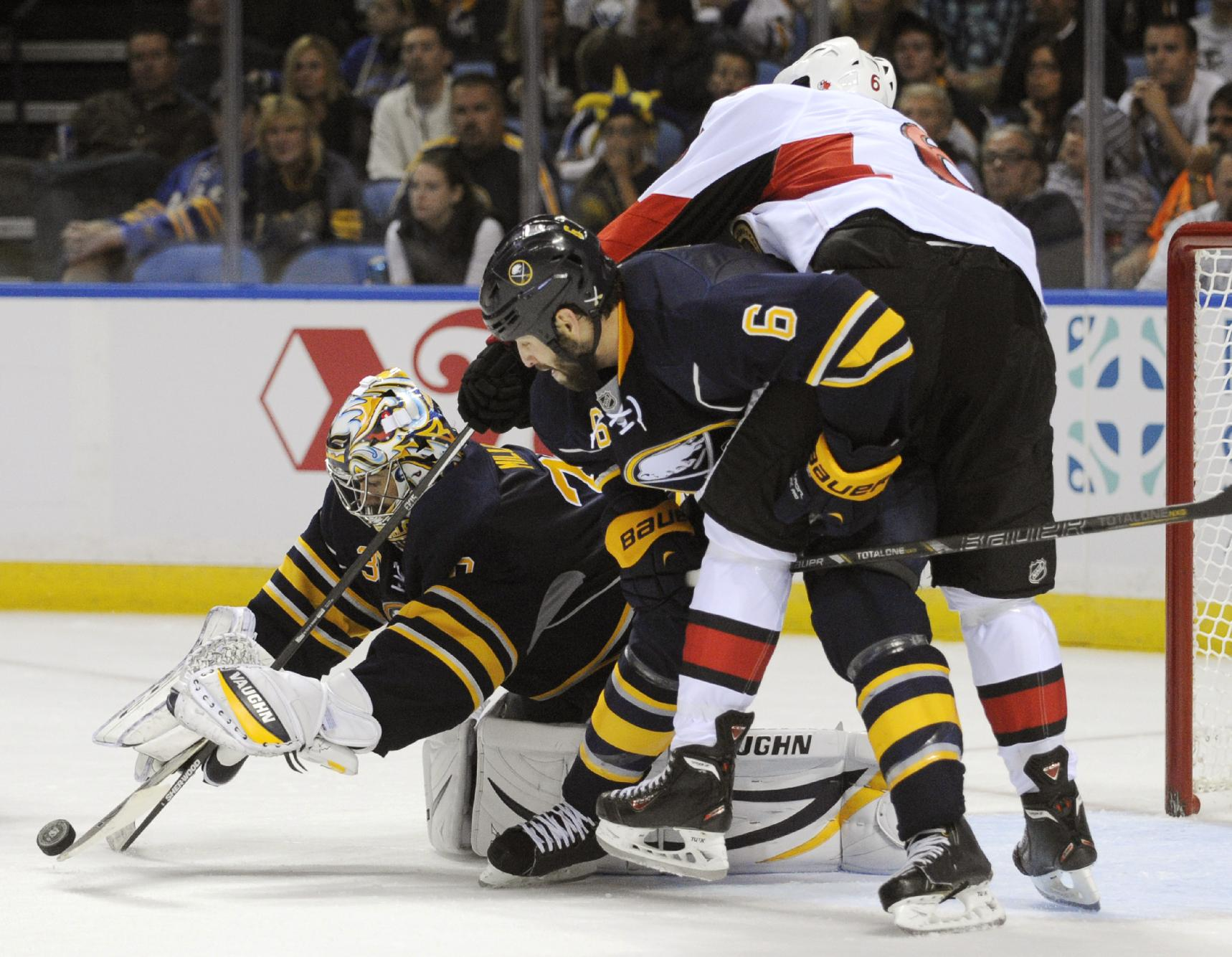 Buffalo Sabres goalie Ryan Miller (30) reaches for the puck as Sabres' Mike Weber (6) checks Ottawa Senators' Bobby Ryan (6) during the second period of an NHL hockey game in Buffalo, N.Y., Friday, Oct. 4, 2013