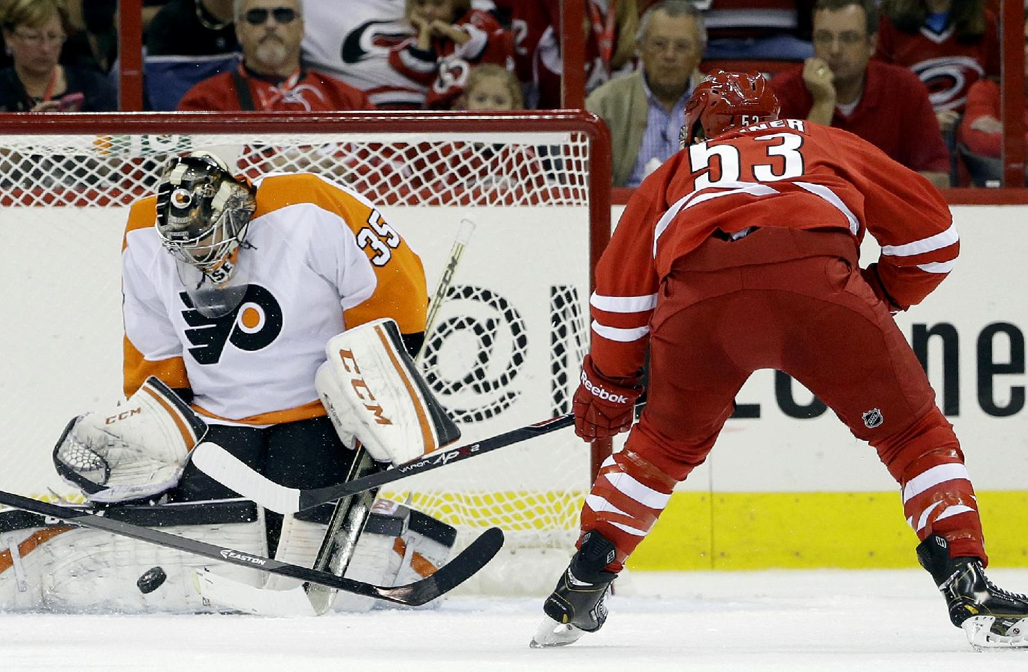 Philadelphia Flyers goalie Steve Mason (35) deflects a shot on goal by Carolina Hurricanes' Jeff Skinner (53)during the first period of an NHL hockey game in Raleigh, N.C., Sunday, Oct. 6, 2013