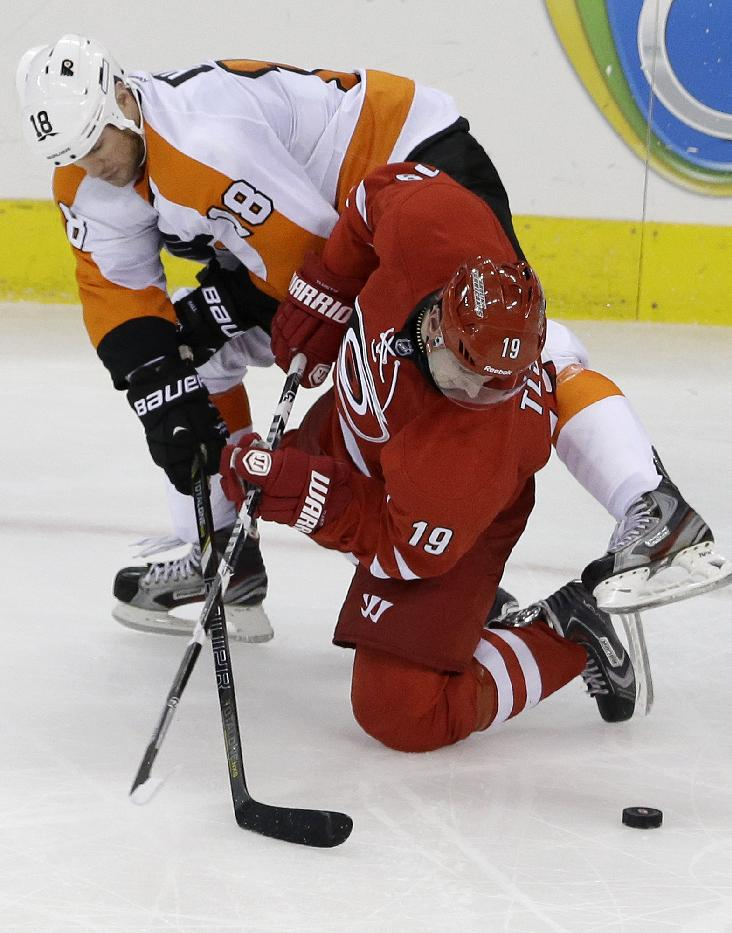Philadelphia Flyers' Adam Hall (18) and Carolina Hurricanes' Jiri Tlusty (19), of the Czech Republic, struggle for possession of the puck during the third period of an NHL hockey game in Raleigh, N.C., Sunday, Oct. 6, 2013. Carolina won 2-1