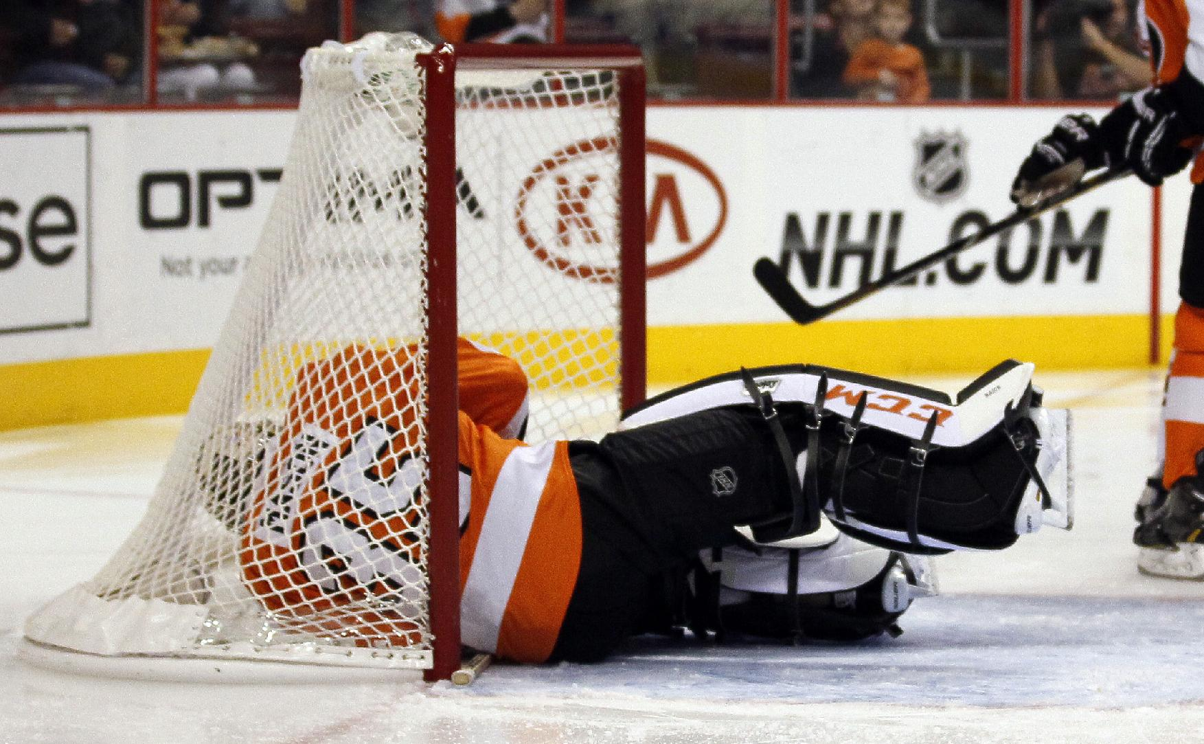 Philadelphia Flyers goalie Steve Mason is down in the net after failing to stop a shot by Phoenix Coyotes' Rob Klinkhammer in the first period of an NHL hockey game on Friday, Oct. 11, 2013, in Philadelphia