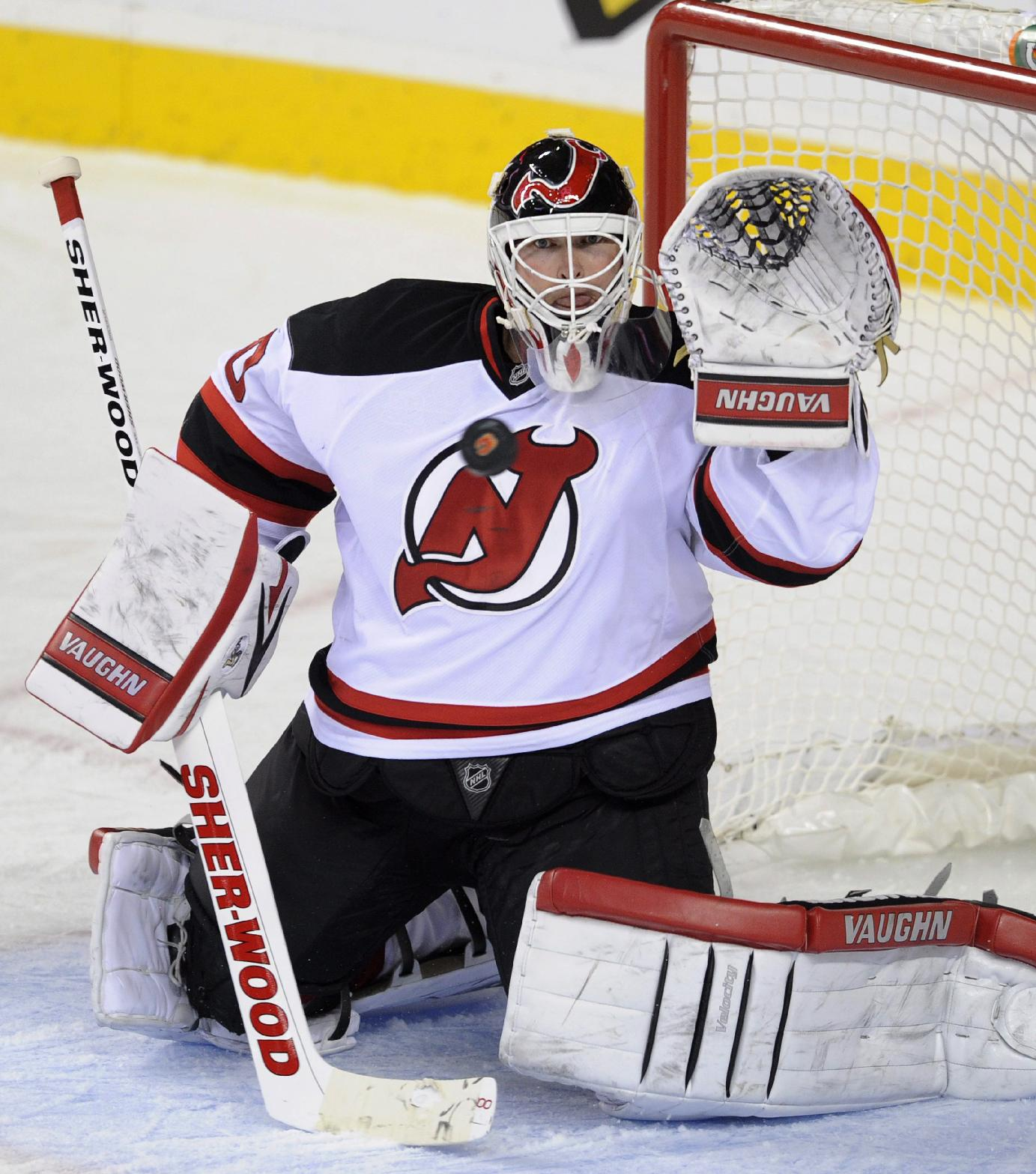 New Jersey Devils goalie Martin Brodeur makes a save on a Calgary Flames shot during the third period of an NHL hockey game Friday, Oct. 11, 2013, in Calgary, Alberta. The Flames won 3-2