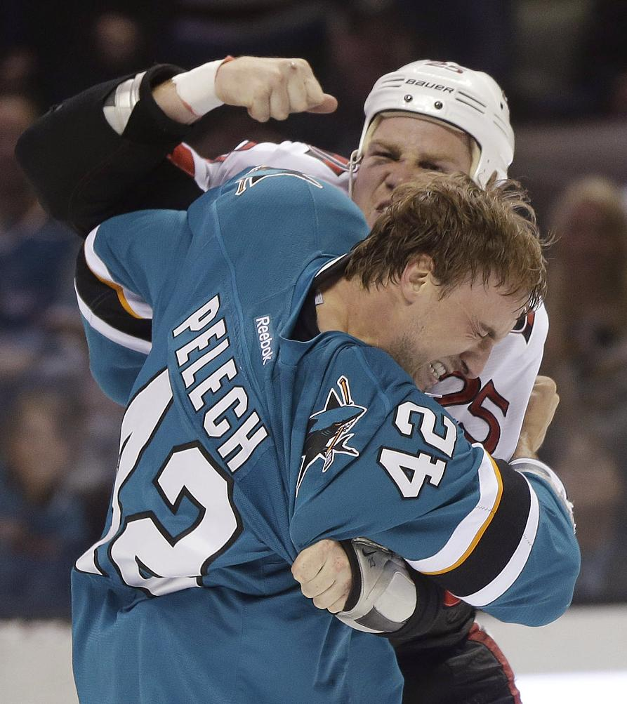 Ottawa Senators' Chris Neil, top, fights with San Jose Sharks' Matt Pelech during the first period of an NHL hockey game Saturday, Oct. 12, 2013, in San Jose, Calif