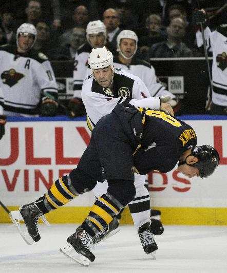 Minnesota Wild defenseman Clayton Stoner (4) knocks Buffalo Sabres center Cody McCormick (8) down during a fight in the first period of an NHL hockey game in Buffalo, N.Y., Monday, Oct. 14, 2013