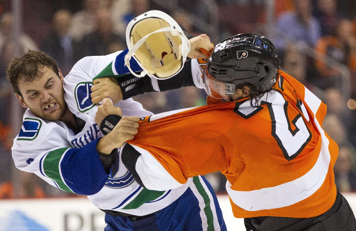Vancouver Canucks' Zack Kassian, left, loses his helmet as he fights with Philadelphia Flyers' Luke Schenn, right, during the first period of an NHL hockey game, Tuesday, Oct. 15, 2013, in Philadelphia
