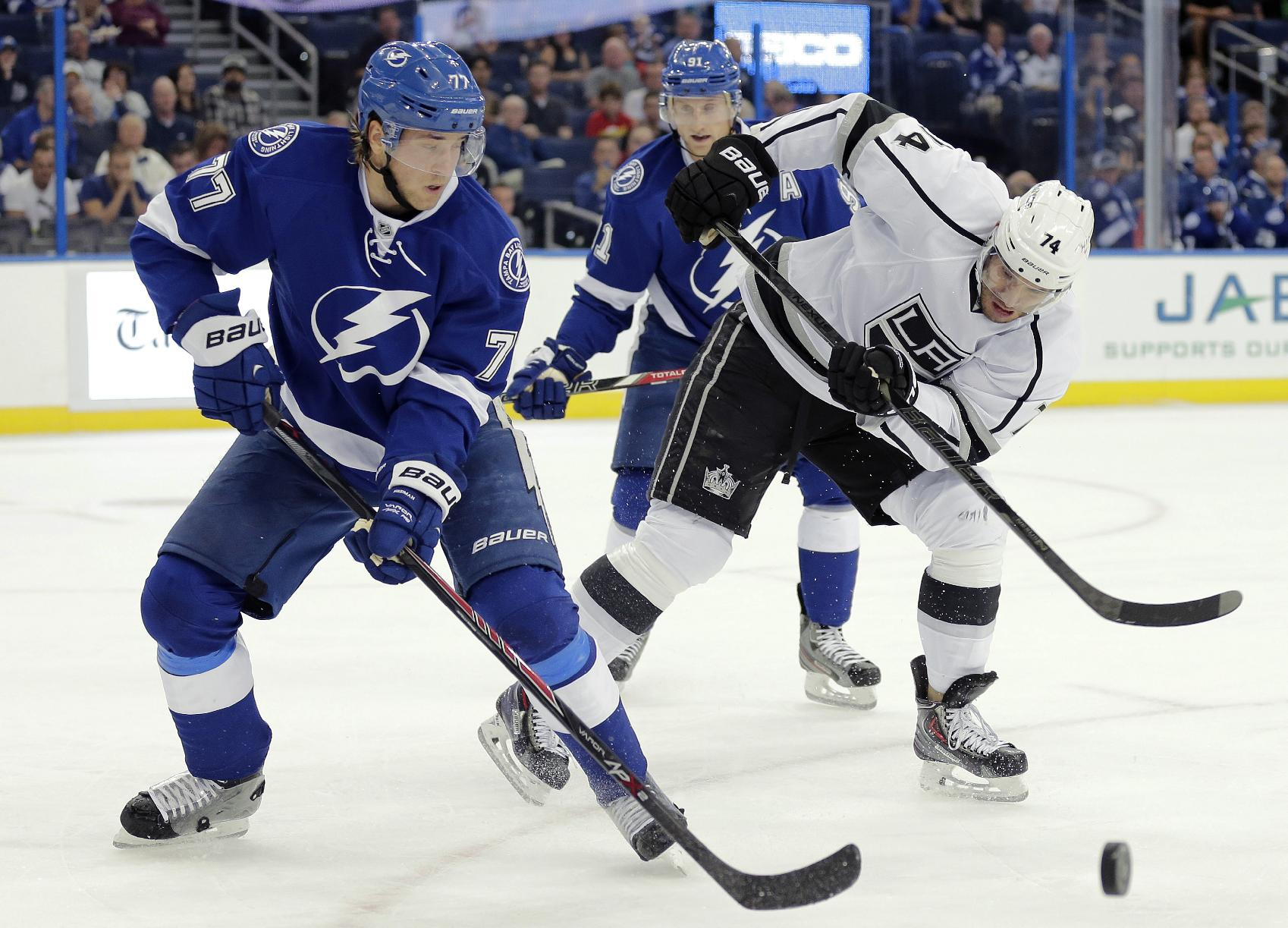 Tampa Bay Lightning defenseman Victor Hedman, left, of Sweden, battles with Los Angeles Kings center Dwight King, right, for the puck during the first period of an NHL hockey game Tuesday, Oct. 15, 2013, in Tampa, Fla