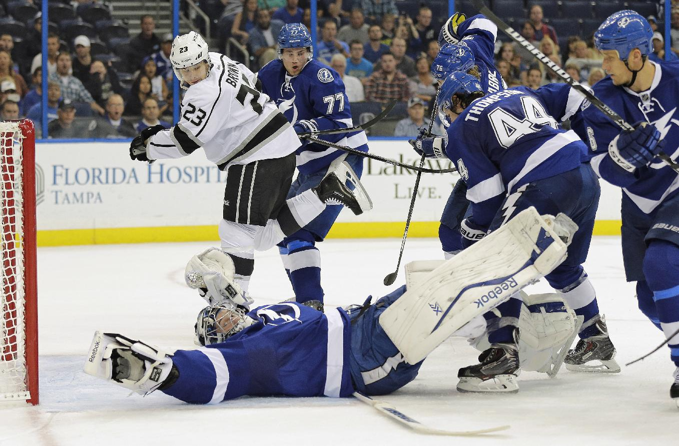 Tampa Bay Lightning goalie Ben Bishop (30) makes a sprawling save on a shot by Los Angeles Kings right wing Dustin Brown (23) as Lightning defenders Victor Hedman (77), of Sweden, Nate Thompson (44) and Sami Salo converge during the first period of an NHL hockey game Tuesday, Oct. 15, 2013, in Tampa, Fla