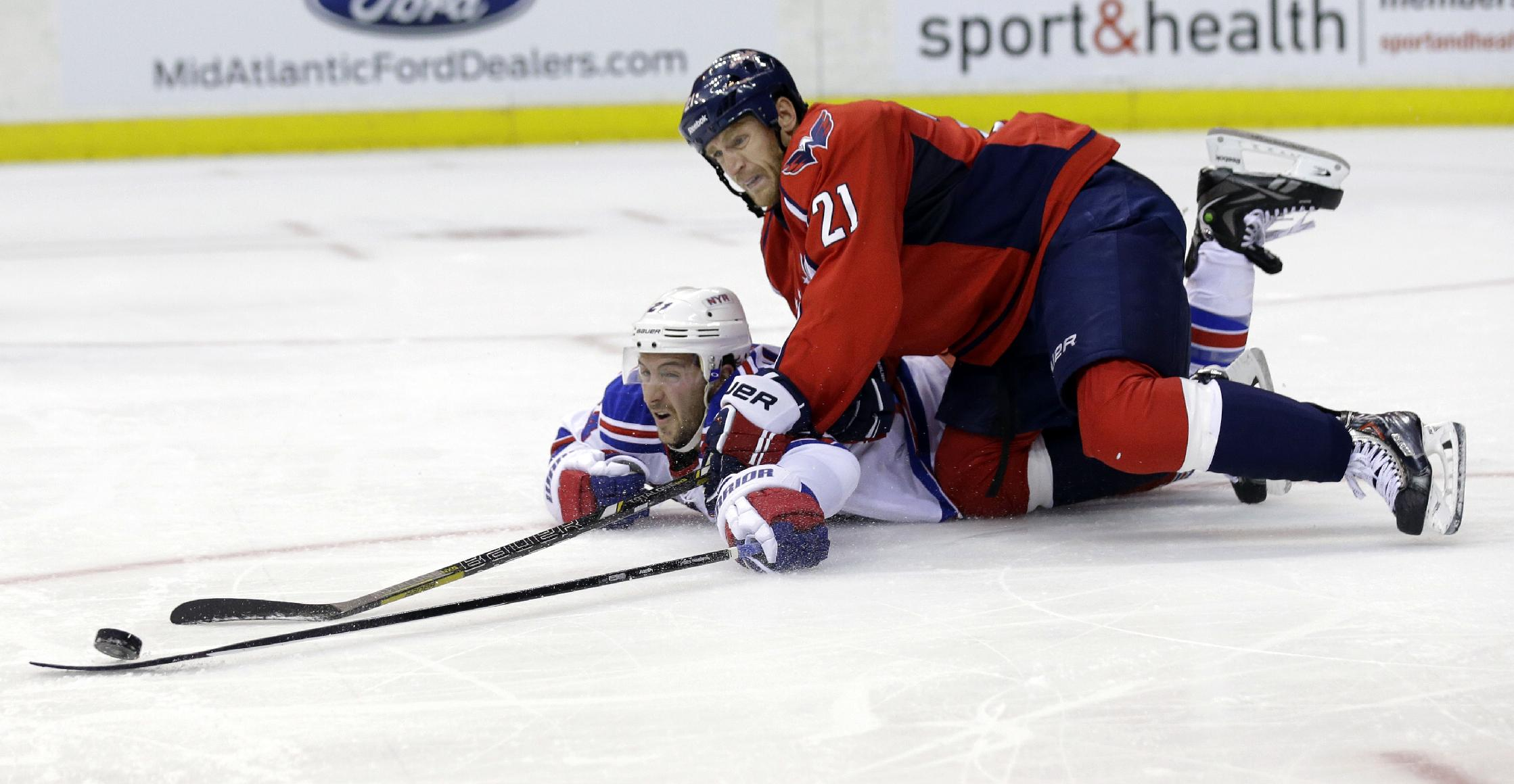 Washington Capitals center Brooks Laich (21) goes over a diving New York Rangers right wing Ryan Callahan in the second period of an NHL hockey game, Wednesday, Oct. 16, 2013, in Washington
