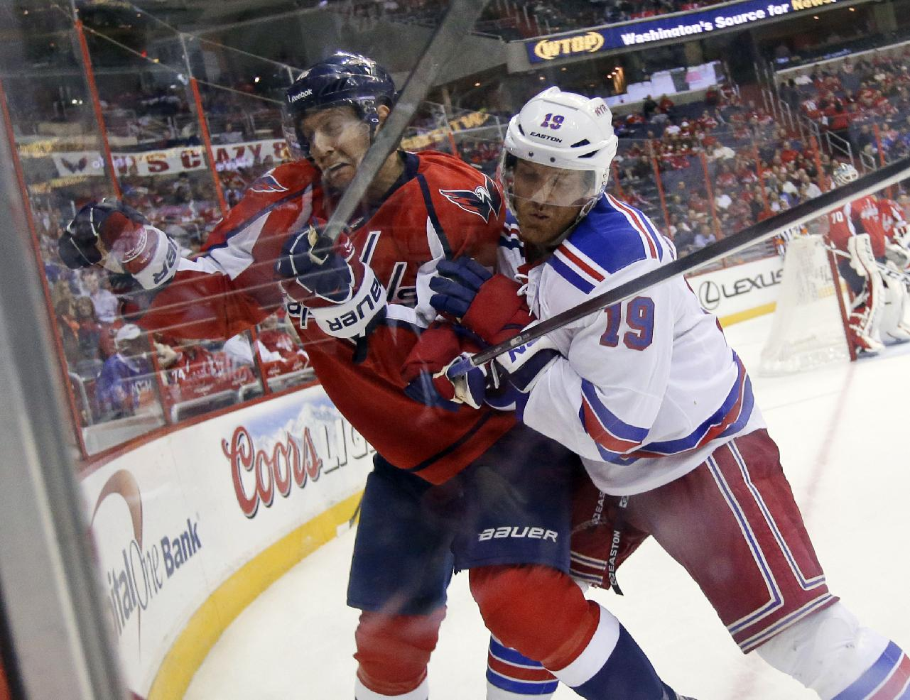 Washington Capitals right wing Eric Fehr (16) is boarded by New York Rangers center Brad Richards (19) in the third period of an NHL hockey game, Wednesday, Oct. 16, 2013, in  Washington. The Rangers won 2-0