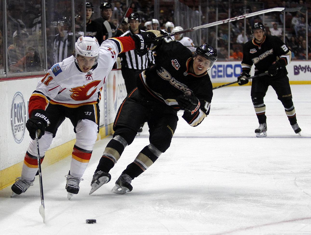 Calgary Flames center Mikael Backlund (11), of Sweden, races to the puck with Anaheim Ducks defenseman Hampus Lindholm (47), of Sweden, during the first period of an NHL hockey game, Wednesday, Oct. 16, 2013, in Anaheim, Calif