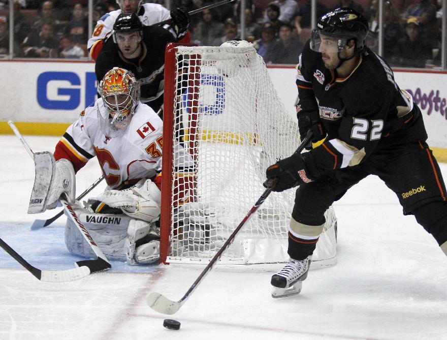 Anaheim Ducks center Mathieu Perreault (22) takes the puck around the net with Calgary Flames goalie Joey MacDonald (35) defending during the second period of an NHL hockey game, Wednesday, Oct. 16, 2013, in Anaheim, Calif