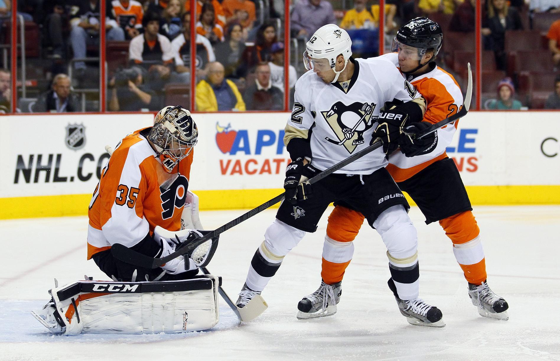 Philadelphia Flyers goalie Steve Mason, left, holds on to the puck as Pittsburgh Penguins' Chuck Kobasew, center, and Flyers' Claude Giroux, right, watch in the first period of an NHL hockey game, Thursday, Oct. 17, 2013, in Philadelphia