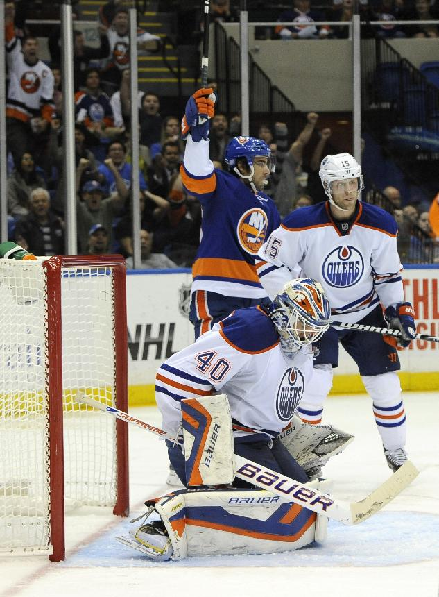 New York Islander' Matt Moulson (26) celebrates Kyle Okposo's goal as Edmonton Oilers goalie Devan Dubnyk (40) and Nick Schultz (15) react in  the second period of an NHL hockey game on Thursday, Oct. 17, 2013, in Uniondale, N.Y