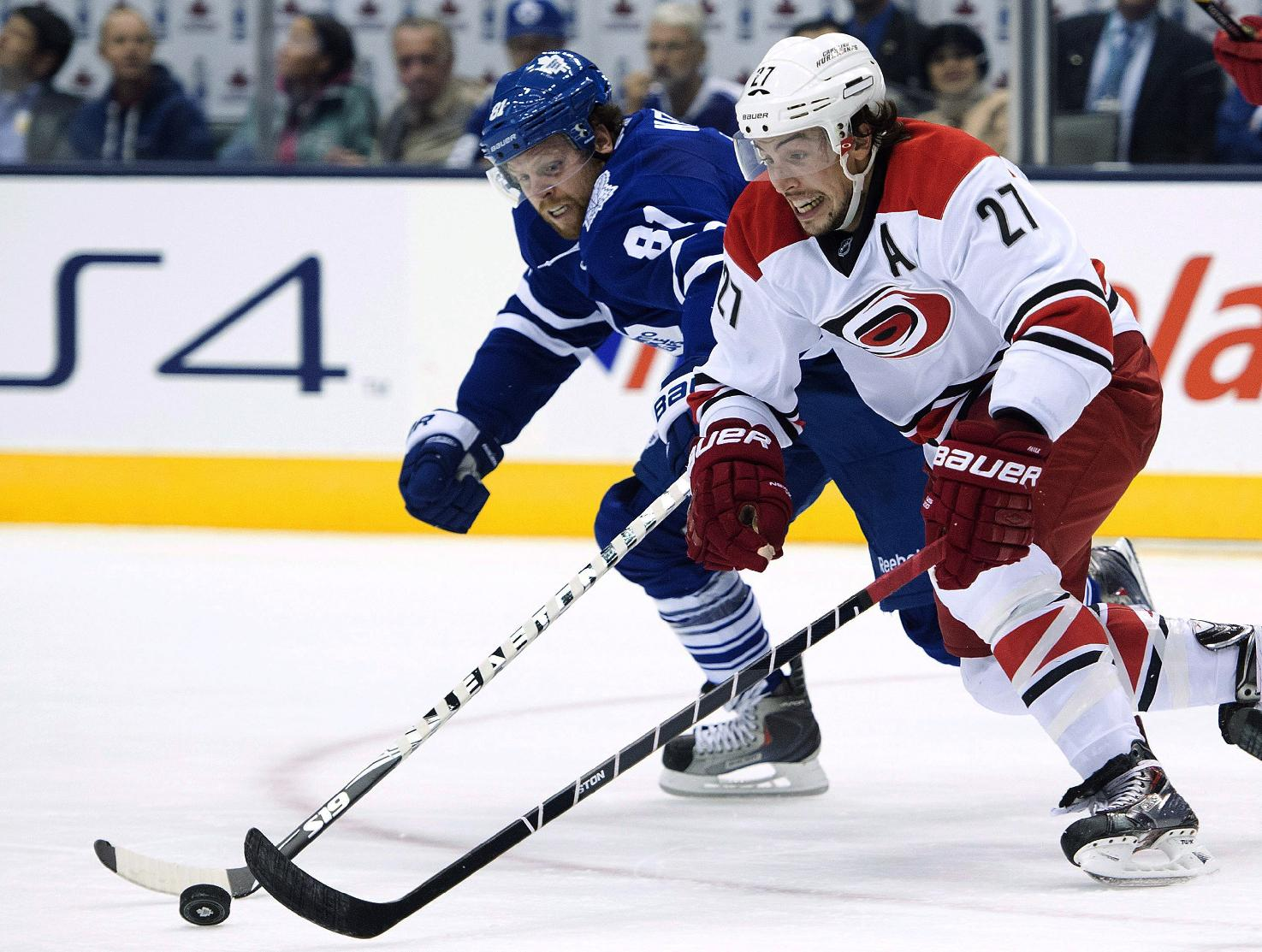 Toronto Maple Leafs forward Phil Kessel, back, chases down Carolina Hurricanes defenceman Justin Faulk during the second period of an NHL hockey game in Toronto on Thursday, Oct. 17, 2013