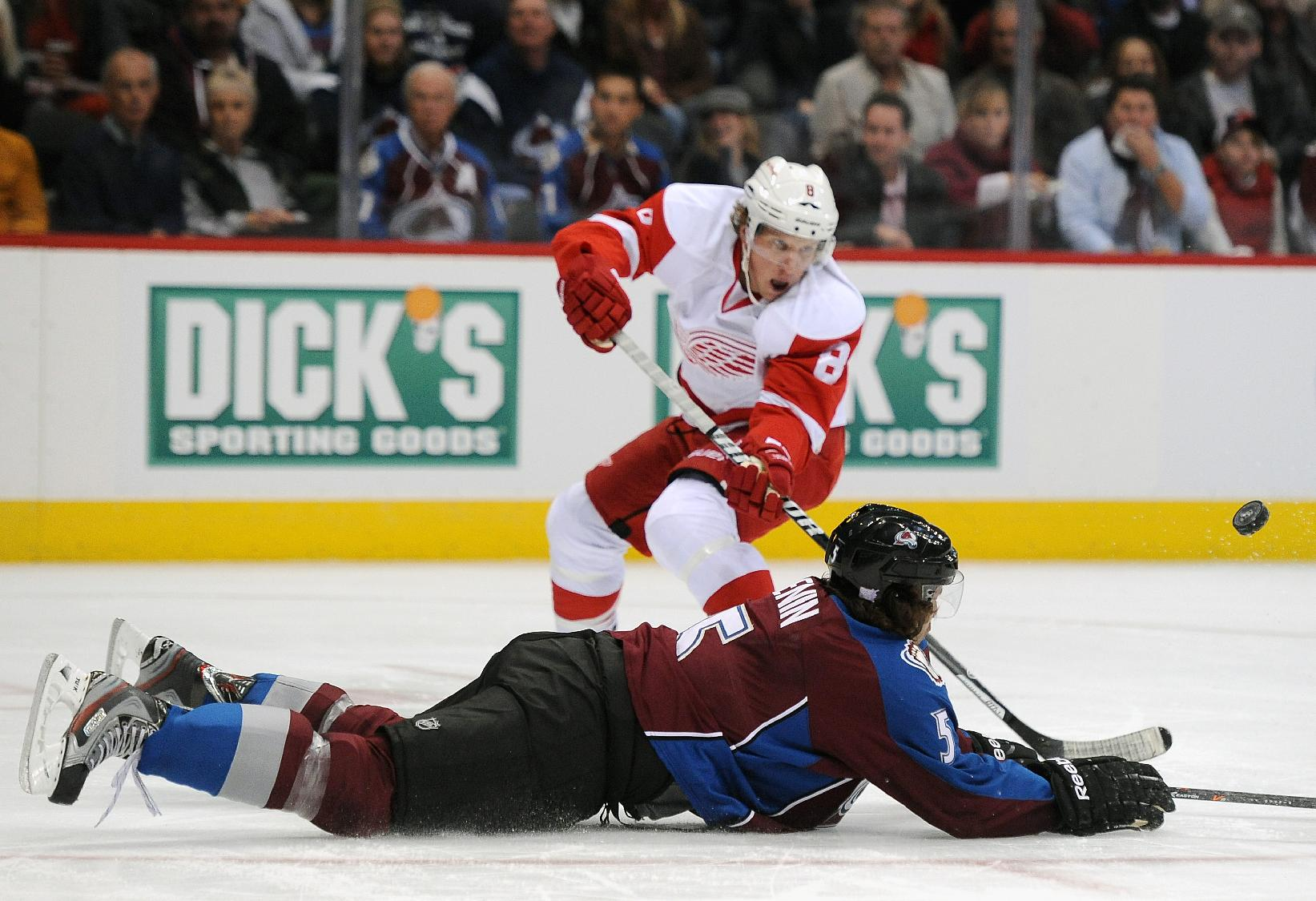 Colorado Avalanche defenseman Nate Guenin, front, lays out to block a shot by Detroit Red Wings left wing Justin Abdelkader, rear, in the second period of an NHL hockey game Thursday, Oct. 17, 2013, in Denver