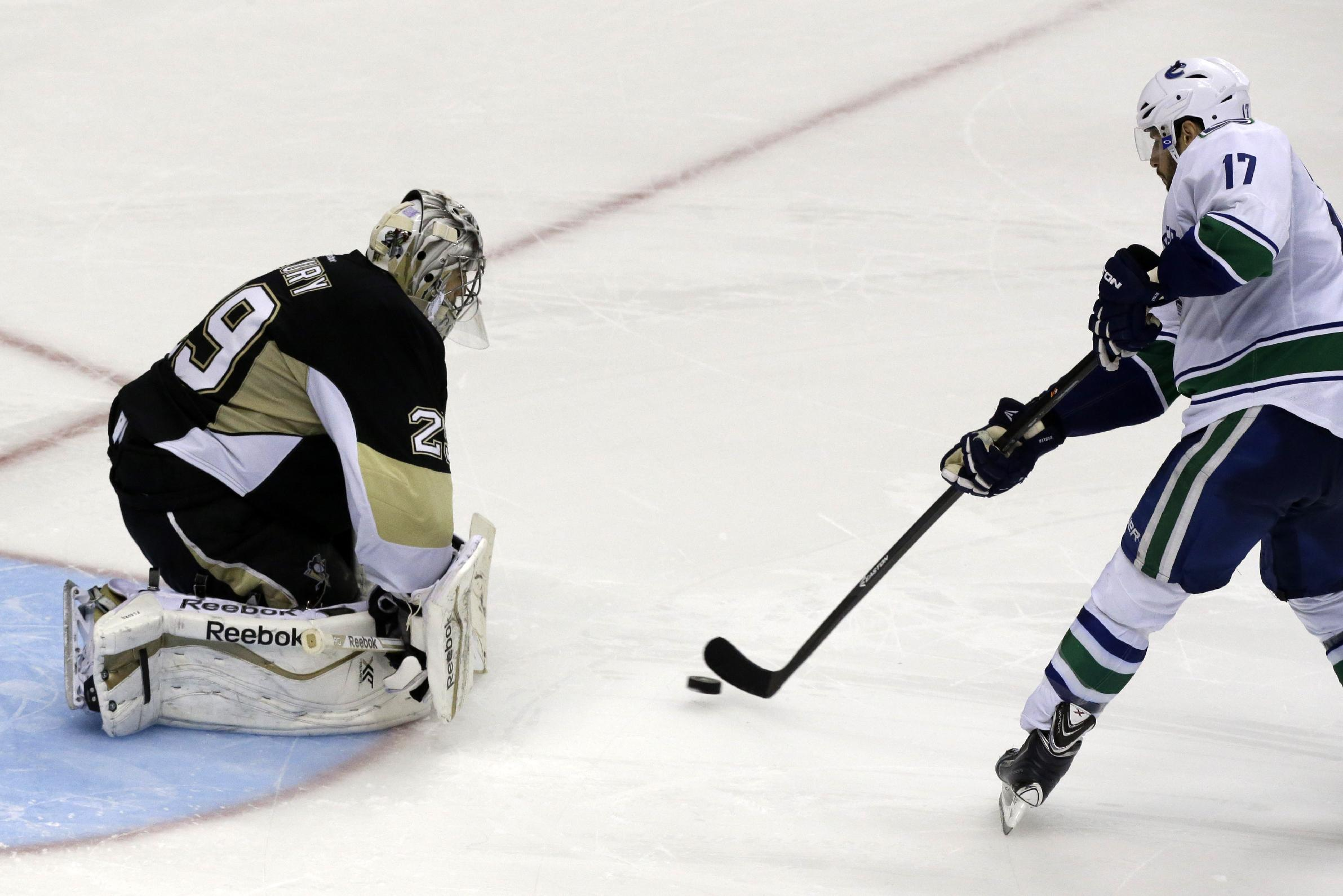 Pittsburgh Penguins goalie Marc-Andre Fleury (29) stops a shot by Vancouver Canucks' Ryan Kesler (17) in an overtime shootout during an NHL hockey game in Pittsburgh Saturday, Oct. 19, 2013. The Penguins won 4-3