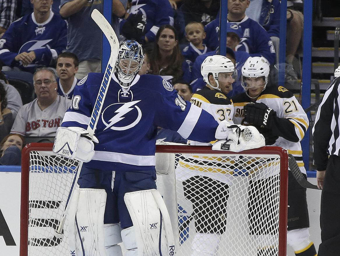 Tampa Bay Lightning goalie Ben Bishop (30) swings his stick as Boston Bruins center Patrice Bergeron (37) celebrates with teammate Loui Eriksson (21), of Sweden, after Bergeron scored a goal during the second period of an NHL hockey game Saturday, Oct. 19, 2013, inTampa, Fla