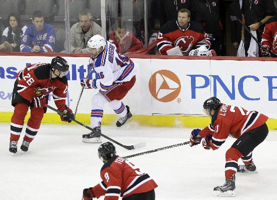 New Jersey Devils goalie Martin Brodeur, center top, looks on during the third period of an NHL hockey game against the New York Rangers, Saturday, Oct. 19, 2013, in Newark, N.J. The Devils won 4-0