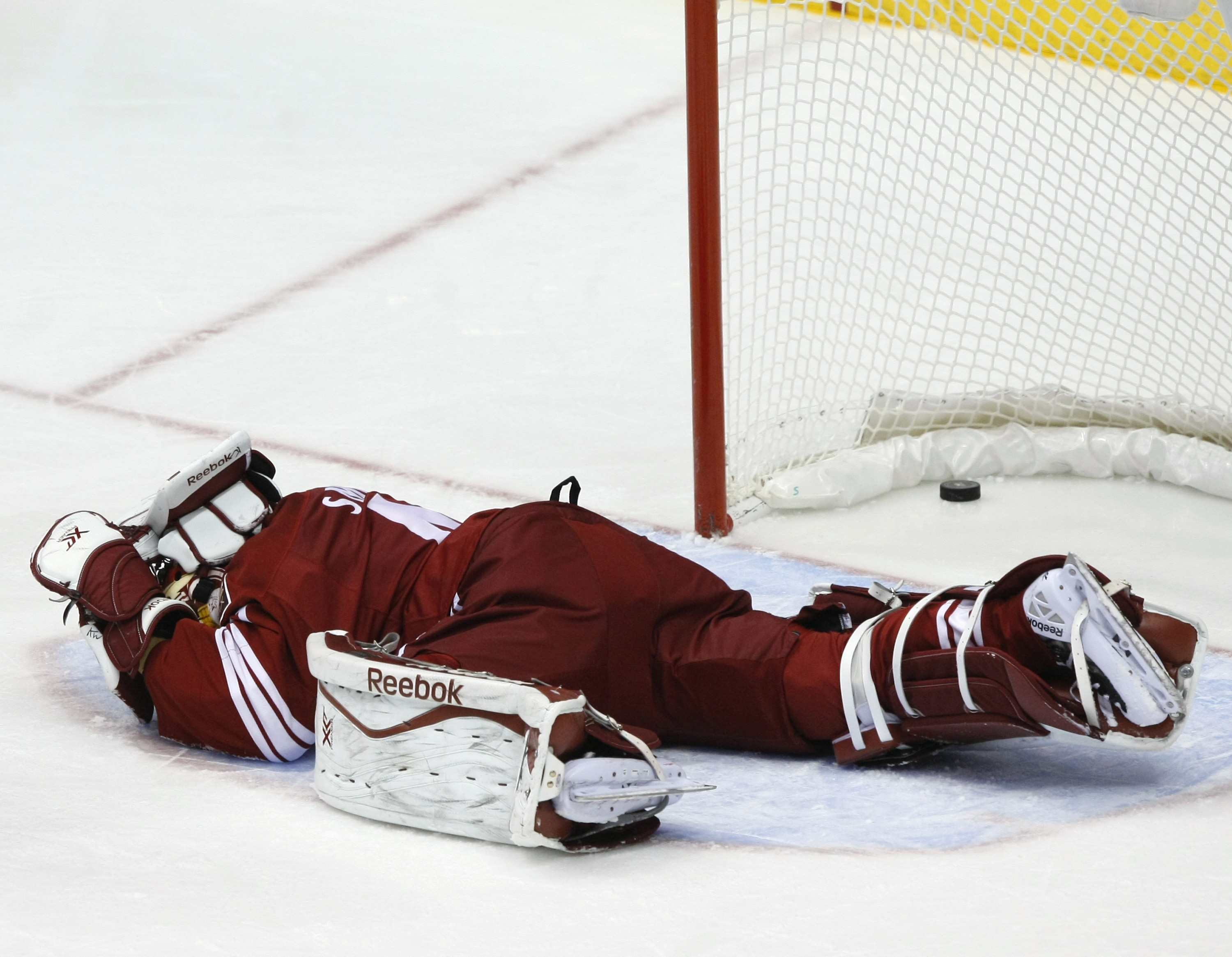 Phoenix Coyotes goalie Mike Smith (41) lies on the ice after getting hit in the second period during an NHL hockey game against the Detroit Red Wings on Saturday, Oct. 19, 2013, in Glendale, Ariz. The goal was disallowed after a review